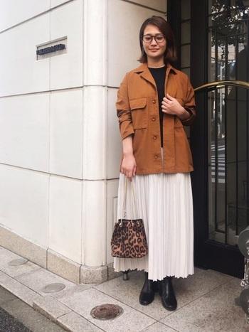 明るいブラウンカラーが大人っぽいワークジャケットに合わせたスカートは、優しいホワイトカラーのプリーツスカート。カジュアルなワークジャケットには一見相性が悪く思える上品なアイテムでも、相性の良い色を合わせれば自然に馴染みます。