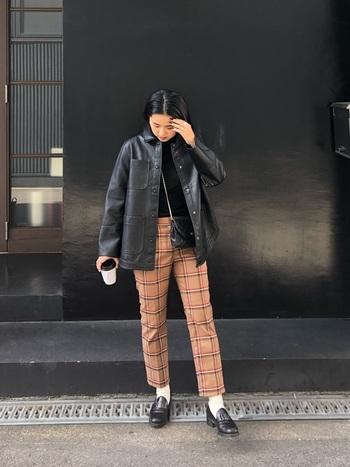 女性らしさを感じるシャネルのバッグに、あえてワイルドなオーバーサイズのレザージャケットを合わせた絶妙なコーデは、おしゃれ上級者のテクニック。ちょっぴりレトロなチェック柄のパンツを合わせることで、シックなヴィンテージバッグと調和して、まとまりのあるスタイリングになっています。