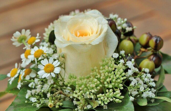 豪華な花束を用意しなくても、ワンコインほどで購入できるお花を上手に使ってミニブーケを作りませんか。こちらは中心にバラ、周りに小花と実もの、放射状に葉ものをあしらったアレンジ。バラは1本のみですが、カラーをしぼることで上品にまとまります。
