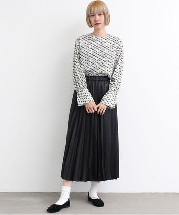 個性的柄ブラウスも、上品な黒のプリーツスカートなら上手に馴染みます。モノトーンなカラー構成やスマートな佇まいが大人な表情。どこかアンニュイな雰囲気漂うモダンなコーデに仕上がっています。