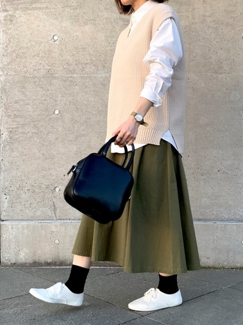 Vネックのベストには、スタンドカラーシャツを合わせてバランス良く。GUのベストは、オフホワイトと細いリブ編みが上質な雰囲気。  きちんと感のある腕時計やミニバッグで、カジュアルなのにシックな装いに。白、黒、カーキと3色使いながらも、配色バランスが絶妙♪