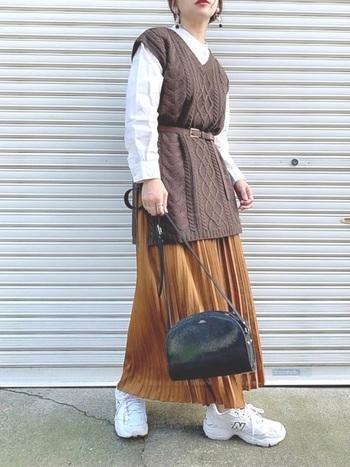 ブラウンのニットベストに、キャメルのプリーツスカートを合わせた秋冬らしいスタイリング。  ベルトでウエストマークすれば、ロングスカートともメリハリのあるこコーデに。ベスト&スカートのロング丈の魅力が引き立つ上級者コーデ♪
