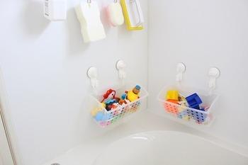 100均のプラスチックかごに細々としたおもちゃを収納。お風呂場の壁に取り付けたフックに掛けておくと、水切りもできて場所も取らず一石二鳥ですね。