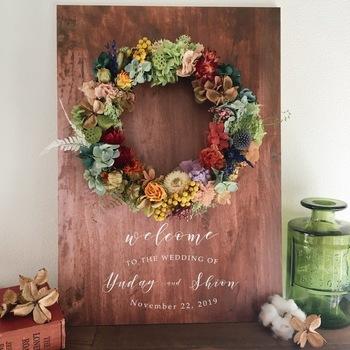 木のパネルにリースをあしらったウェルカムボード。プリザーブドやドライにできるお花を選んで、ぜひ結婚式の後も飾って楽しんで!
