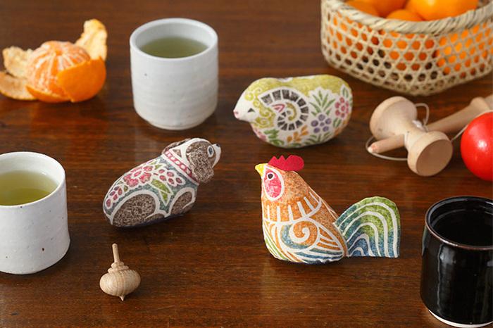 木版手染という手法で染められたぬいぐるみは、優しい色合いと独特のデザインが懐かしくも温かみがあります。綿で出来たぬいぐるみの中には、籾殻がぎっしりと詰まっていて、丸みのあるフォルムと独特の手触りを作っています。