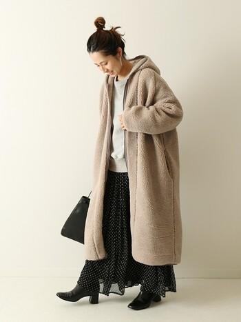 軽い質感のフレアースカートにオーバーサイズなフード付きボアコートをラフに羽織って。無造作にまとめたヘアとも良いバランスです。