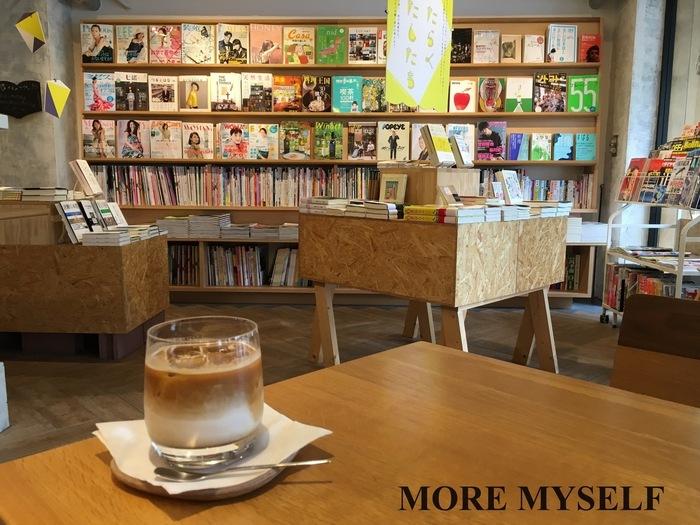 """壁面の書棚はさまざまな雑誌に彩られ、書棚も、リコメンド本を集めた棚、紹介文だけの""""シークレット棚""""まで、興味を持たせる仕掛けも凝らされて。ブックカフェではないため、テーブルで読めるのは購入した本になりますが、前出の〈棚〉によって、思いがけない本との出会いがあるかも。"""