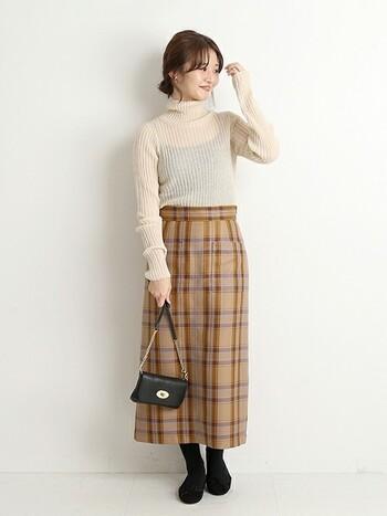 キャメルカラーのスカートには、アイボリーのニットを合わせて調和を楽しんで。小物はタイツと同じ黒で揃えてスッキリと。