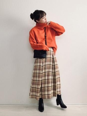 大きいタック&シルエットのスカート。明るいカラーのスカートなので、ニットもオレンジカラーで元気はつらつと。小物を引き締めカラーで統一すれば子供っぽくなりません。