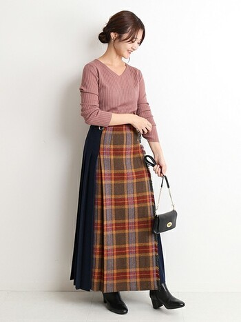 サイドがプリーツ状になったチェックスカート。優し気なピンクのニットを合わせれば、着こなしが難しそうに見えるスカートもお洒落度を上げる立役者に。