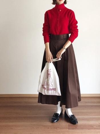 赤のタートルニットとカーディガンのアンサンブル風のトップスに、ダークブラウンを合わせたコーディネート。スカートの色味はもちろん、トップスインや白の靴下でレトロな雰囲気を演出しています。