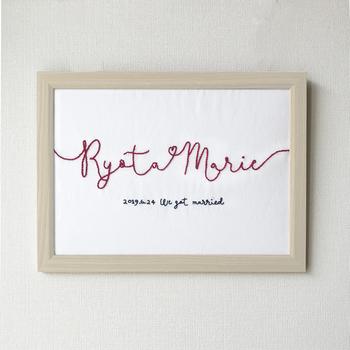 結婚式らしく、ふたりの名前を一筆書きにして赤い糸で刺繍されたウェルカムボード。縁起がよくて、可愛さもばつぐんです♡