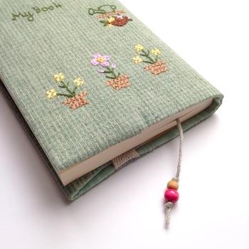 小さな裏庭の風景をイメージしたクロスステッチが可愛いブックカバー。カバーにしおりが付いた気の利いた作りになっています。
