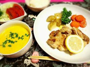 かぼちゃスープの濃厚さを生かして、さっぱりとしたおかずを合わせるのもひとつの方法。こちらは、レモンソースのかかったチキンステーキがメインです。付け合わせの野菜とさらにサラダも加えて、野菜たっぷりの献立に♪