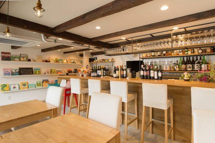 梁の存在感を活かしながら、現代に合うモダンな雰囲気を取り入れた店内。カウンター席、テーブル席、座敷席があり、壁一面には絵本がずらりと並んでいます。