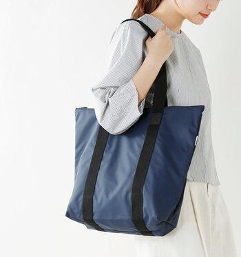 軽量な素材で作られた、ネイビーの大きめトートバッグ。撥水加工と上部のファスナーで、雨や雪から荷物をしっかりと守ってくれます。濡らしたくないバッグを、このトートバッグにすっぽりと入れてしまう使い方もおすすめです。