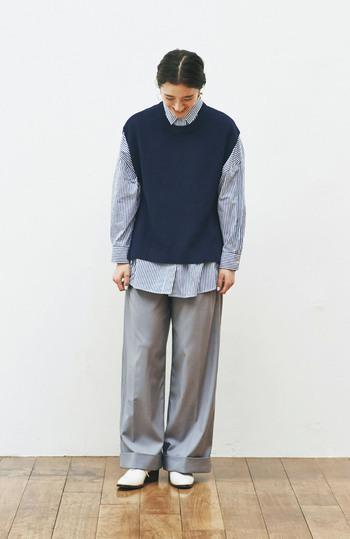 ネイビーのニットベストに、同系色のストライプシャツをレイヤードしたコーディネート。ボトムスはグレーのワイドパンツで、ちょっぴりメンズライクなスタイリングに。足元の白シューズで、爽やかさをさりげなくプラスしています。