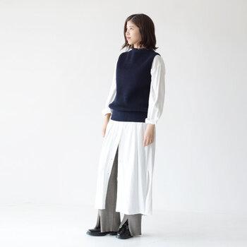 白のシャツワンピースに、ネイビーのニットベストを重ねたコーディネート。ワンピースのボタンを少し多めに開けて、グレーのワイドパンツを覗かせたフェミニンな着こなしに仕上げています。