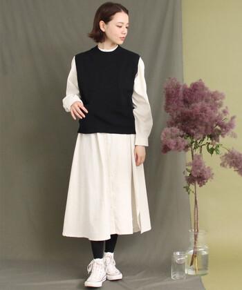 白のシンプルなシャツワンピースの上に、黒のニットベストをレイヤードした着こなしです。タイツはニットベストと、シューズはワンピースとそれぞれ色を合わせて、ナチュラルなモノトーンコーデに。