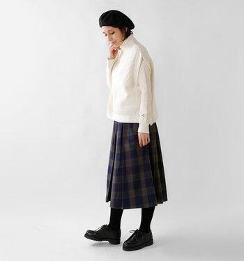 白のニットベストに、白の長袖トップスを合わせた着こなし。一枚のトップスのように見える、さりげないレイヤードがおしゃれ感をアップしてくれます。チェック柄のスカートをメインに、小物を黒でまとめた大人の冬コーデです。