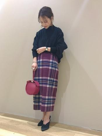 綺麗なパープルのチェックスカートは、黒のニットを合わせてすっきりと。バッグもやや青みがかった色味のものを選べば、スカートにもしっかり馴染みます。