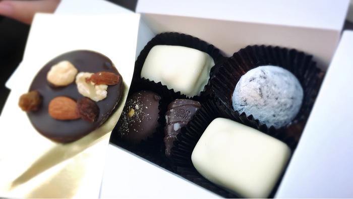 レオニダスの箱に詰め合わせてもらえば、立派なプレゼントに。  一番人気なのがホワイトチョコレートで、ホワイトチョコレートのなかでも「マノンカフェ」が断とつ人気。ココアバター100%のホワイトチョコレートで、ヘーゼルナッツで包んだ逸品です。リピーターが多いそうで、ホワイトデーにも人気。これを口にすると、ホワイトチョコレートのイメージが変わるかもしれませんよ。  また、冬限定の生チョコトリュフ、定番のプラリネも、みんな大好きな味わいで、オススメです。