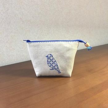 鳥のモチーフの中にクロスステッチを施したデザインポーチ。青一色でシンプルながらも存在感のあるデザインです。
