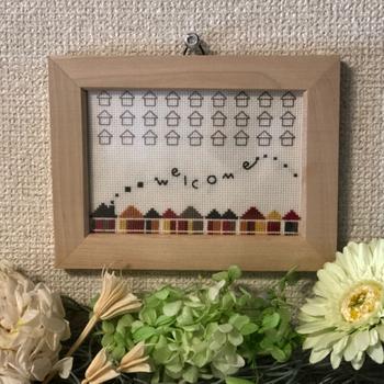 """煙突から""""welcome""""の文字が躍るように描かれています。ほっこりするモチーフのウェルカムボードを玄関に飾ってみませんか?"""