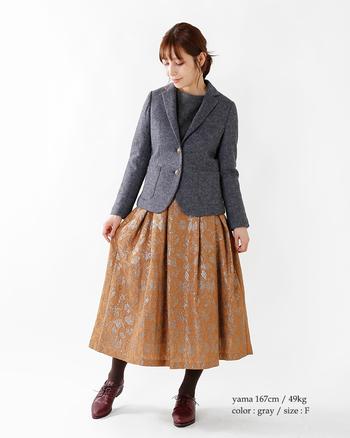 厚めのウールテーラードジャケットに光沢ある華やかな柄物スカートをあわせて、品のある女性らしいコーディネートに。足元もクラシカルに落ち着いた雰囲気で、オフィスにもやおでかけにもぴったりです。