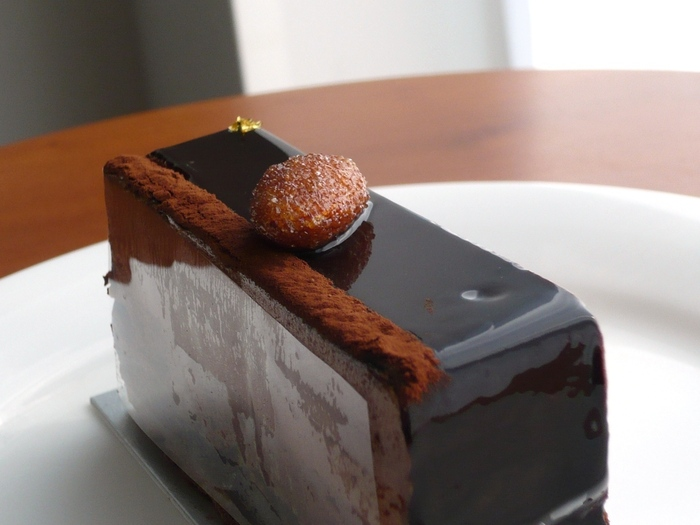 こちらの「アンタンス」も、アテスウェイのチョコレート系ケーキのなかで、高い人気を誇ります。  62%のカカオを使用したムースとガナッシュによる、とっても濃厚なチョコレートケーキ。なめらかなだけではなく、砂糖がけのアーモンド、下のほうにあるザクっとした生地が、食感を楽しませてくれます。