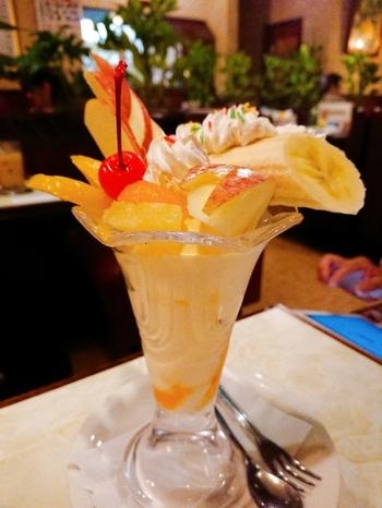 """""""フルーツパフェ""""は、アイスクリームの上に黄桃とバナナ、パインにチェリー、うさぎや木の葉型のリンゴが華やかに盛り付けられています。グラスからはみだすバナナに添えられたホイップクリームとカラースプレーがなんともレトロで、女性心をくすぐります。"""