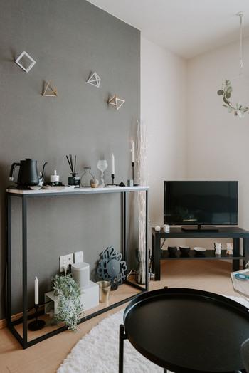 壁際に置かれたコンソールテーブルの上には、ブラックで統一された雑貨と、背の高いキャンドル。 高低差をつけて、バランスの良いディスプレイに仕上がっていますね。  キャンドルホルダーは他の雑貨に合わせてブラックに。 形の選び方もおしゃれですね。  コンソールテーブルの細身の脚台、バルミューダケトルの細いノズル、繊細なワイヤーアート……。 線の細いフォルムのアイテムでまとめられています。