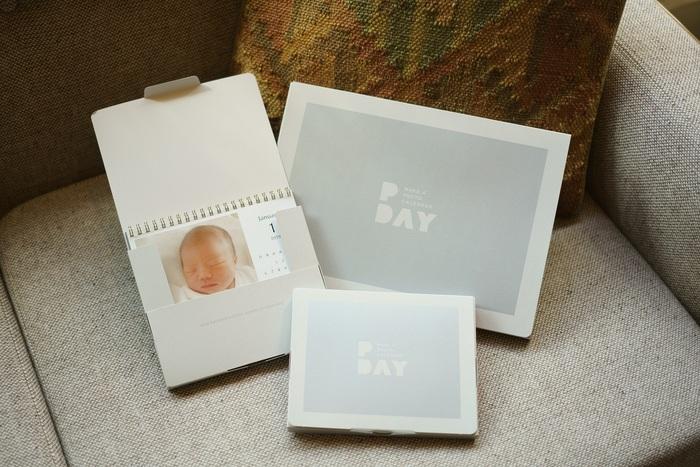 """最近は年賀状の発行枚数が年々減少*し、新年の挨拶も多様化しているのかもしれません。そのひとつとして、子どもの写真をカレンダーにして両親へ送る素敵な挨拶も『PDAY』なら実現できます。 一冊であればメール便対応で格安に配送でき、開封するとおしゃれなパッケージに入った愛しい孫のカレンダーが出てくる""""サプライズ""""が贈れるのです。 また、取り扱い店舗では店内仕上げが最短30分。帰省前日にふと思い立っても間に合うスピード感です。"""