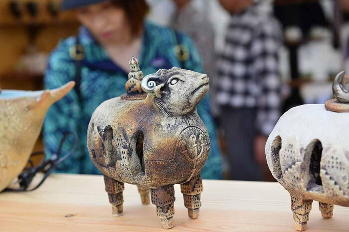 """「笠間焼」は、""""民藝""""調の益子焼とは異なり、作家や窯元にそれぞれの個性が際立ち、""""多彩""""であることが大きな特徴となっています。かつては、他の窯業地同様に地元の土を用い、地域の人々によって焼かれていましたが、全国から作家が集う現在の「笠間」では、自由に作陶する気風が定着し、各々の作品に合わせて、様々な土や釉薬が用いられています。【2019年の「陶炎祭」に展示された笠間の陶芸作家・須藤忠隆(東風舎)の作品】"""