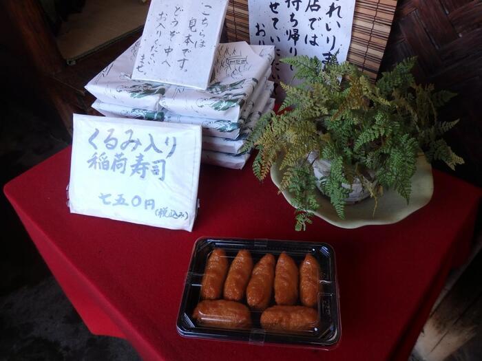 白い狐の看板が目印の、創業110余年を数える鳥居前の名物寿司店「二ツ木」は、稲荷寿司の専門のテイクアウト店。昼食の弁当、土産購入にお勧めのお店です。