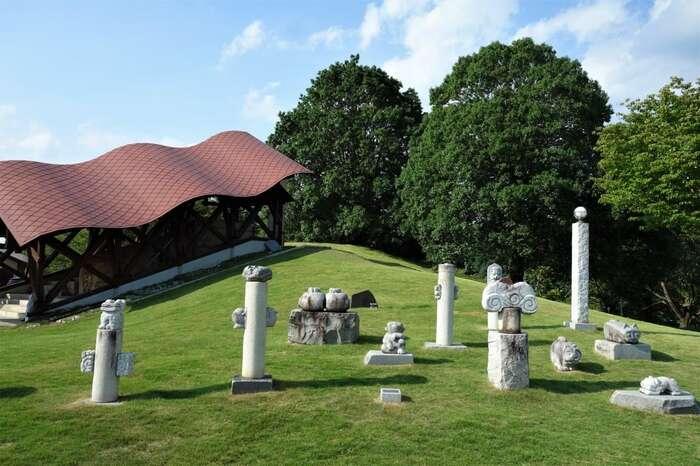 「笠間芸術の森公園」の西側の小高い丘にあるのが、笠間焼の複合施設「笠間工芸の丘」です。 【「笠間陶芸の丘」(画像奥の建物は、年に一度、薪が焼べられる「登り窯」)】
