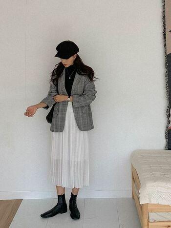チェックのテーラードジャケットに風に揺れる白いプリーツスカートで、春を感じるスタイリング。インナーや小物は黒で合わせてコーデ全体を引き締めています。ハンチング帽もチェックのジャケットと相性が良く、クラシカルな雰囲気。