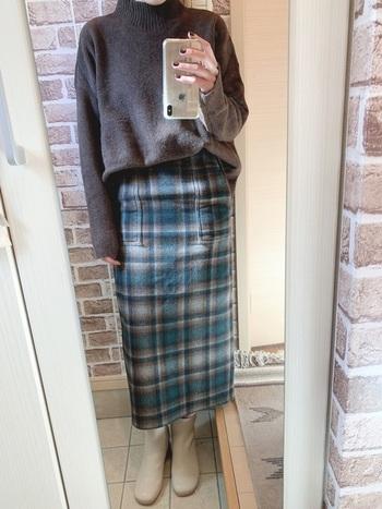 落ち着いたグレーのニットに、チェック柄のタイトスカートを合わせてトラッド感のある着こなしに。ニットはフロントインしてスッキリ着ると全体のバランスが整います。