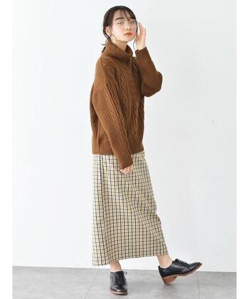 伝統的なケーブル編みは、ややゆったりとしたサイズ感を選ぶのも華奢みせのポイント。ブラウンのニットとチェック柄スカートの合わせ方は、どこか懐かしいレトロっぽさを演出。ラフにまとめたヘアスタイルもマッチしています。