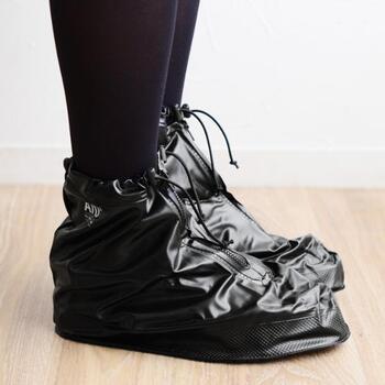 靴の上から履いて使用する、A/D2のシューズレインカバー。今ある靴にプラスアルファするだけでOKな、お手軽レイングッズです。フロント部分のチャックを開けて足を入れ、足首の締まり具合を調整すれば装着完了です。