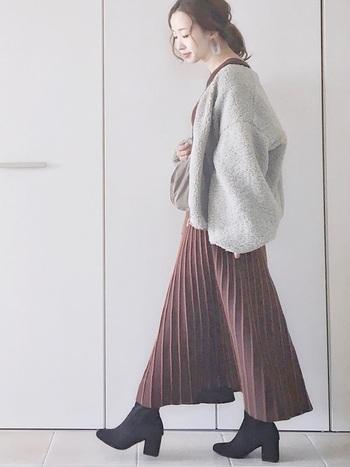 ロングプリーツワンピースにオーバーサイズのボアジャケットを羽織ったスタイル。ノーカラーが上品で、袖のボリューム感が旬のシルエットを作っています。