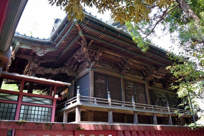 「笠間稲荷神社」の見所は、神社建築の美と現代建築が融合した「拝殿」や、入母屋造りの「東門」、樹齢400年にも及ぶ拝殿前の「藤棚」等様々にありますが、中でも素晴らしいのが、江戸末期建立の「御本殿」。国の重要文化財に指定された入母屋造りの本殿は、地元大工や彫工らによって丁寧に作られています。とりわけ素晴らしいのが、精巧に施された壁面の彫刻です。