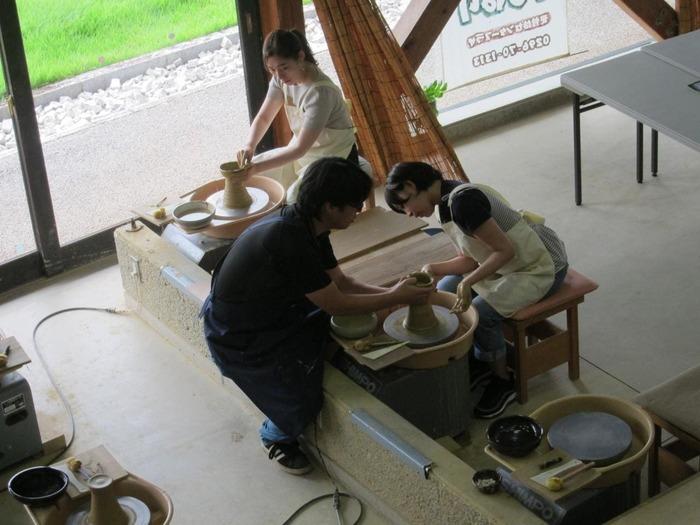 """中でも人気なのが、""""ろくろ""""や""""手ひねり""""、""""絵付け""""といった陶芸を気楽に挑戦できる「陶芸体験」です。基本料金も焼成代もリーズナブル。インストラクターの指導付きで、ちょっとやってみたいなという方にお勧めです。  【「笠間工芸の丘」内にある体験施設「ふれあい工房」(画像は「ロクロ体験」コース】"""