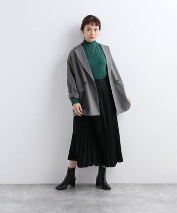 ダブルボタンのドロップショルダーになったトレンド感あるジャケットに黒スカートを合わせたきちんとコーデ。インナーにグリーンのハイネックのニットが映える冬のスタイルです。
