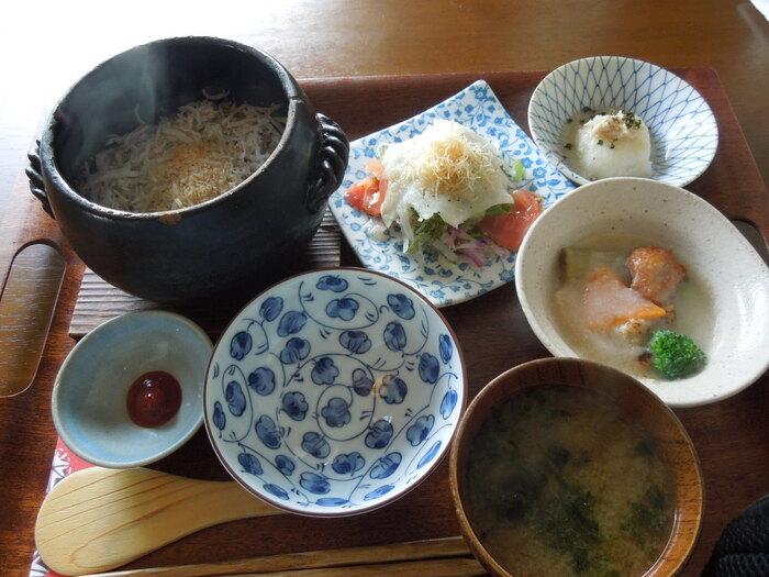 【釜揚げしらすの土鍋ごはん】 ランチメニューで注文できる「土鍋ご飯」。全ての土鍋ご飯は、3種の小鉢とお味噌汁がセットになっています。  3種の小鉢は、季節ごとに旬の食材や地元の野菜を使ったお店オリジナルの創作料理。真心こめて作られた小鉢は、素材の旨味がいきた上品な味わいを楽しめます。