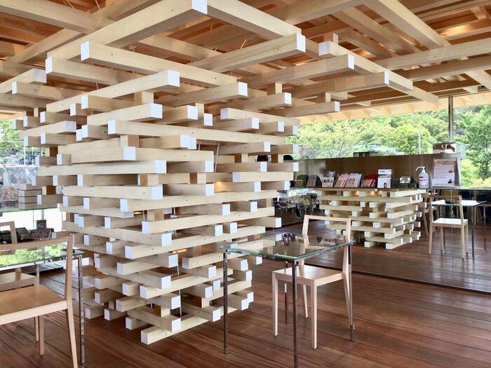 内部も隈研吾さんのこだわりが詰まっています。「大きな木の下に人々が集う建築」というコンセプトのもと、1500本ものアラスカヒノキを組み上げた木組みが中央に据えられています。鏡で作られた家具は、自然と木の質感を映し出し、ナチュラルに存在しています。