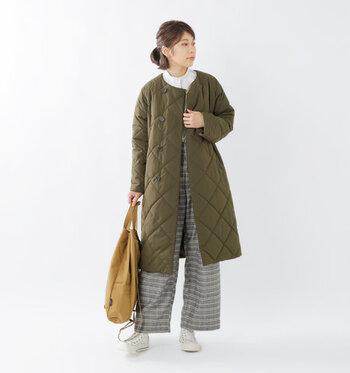 オリーブグリーンカラーの着る絵Tリングコートに、チェック柄のワイドパンツを合わせた着こなし。トップスは白のブラウスで、カジュアルと上品のミックスコーデにまとめています。ベージュのバッグが、程よいアクセントカラーに♪