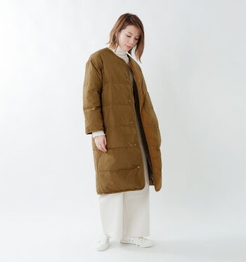 オレンジブラウンカラーの、明るめダウンコートに白のワイドパンツを合わせたスタイリング。トップスも白のタートルネックで、インナーコーデをワントーンで揃えています。シューズも白で爽やかにまとめて、ダウンコートが主役な大人の冬コーデですね♪