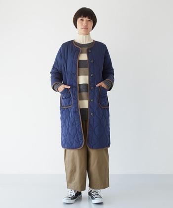 ネイビーのキルティングコートに、ベージュのワイドパンツを合わせたナチュラルなコーディネート。ボーダー柄のハイネックニットが、季節感たっぷりなコーディネートを演出しています。寒い時期にはタイツやレギンス、ストールやマフラーを合わせても◎。