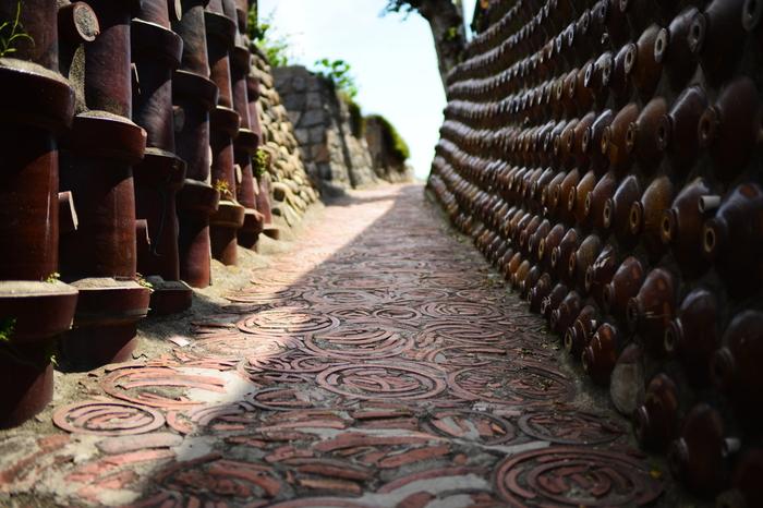 土管坂は、やきもの散策道を代表する景観の一つです。急勾配の坂道の擁壁には明治期に常滑市で生産されていた土管と昭和初期に生産されていた焼酎瓶がびっしりと埋め込まれています。また坂道には土管焼成時に使用した廃材、「ケサワ」が敷き詰められており、独特の風景が広がっています。